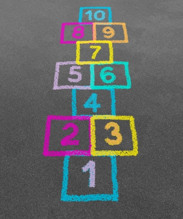 Hopscotch in a schoolyard on an asphalt floor with chalk drawings of numbers and squares as a symbol of youth innocence and children playing a fun play ground jumping game at recess or after elementary school