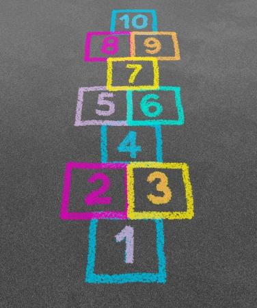 Rayuela en el patio de una escuela en un piso de asfalto, con dibujos de tiza de números y plazas como símbolo de la inocencia de la juventud y los niños que juegan un juego divertido juego de tierra saltando en el recreo o después de la escuela primaria Foto de archivo - 13559417