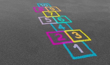 innocence: Hopscotch game in perspective in a schoolyard on an asphalt floor with chalk drawings of numbers and squares as a symbol of youth innocence and children playing a classic jumping tradition at recess or after elementary school
