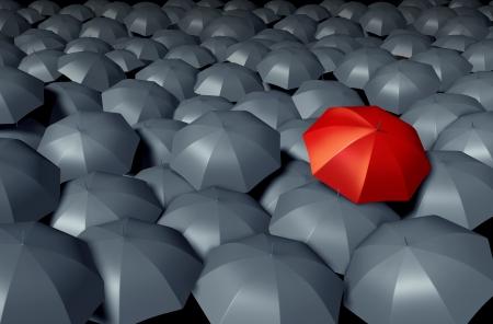 Salirse de la multitud con un paraguas rojo contra un grupo de sombrillas grises como un concepto de negocio de la tormenta el tiempo de protección único y diferente y la seguridad Foto de archivo