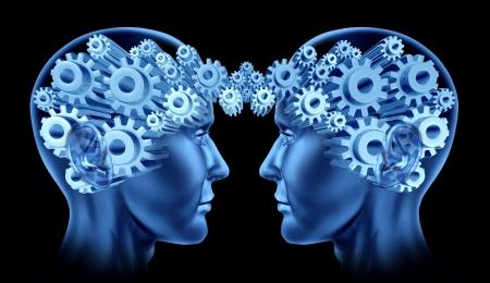 El trabajo en equipo y la cooperación empresarial con dos cabezas humanas frente a frente con los engranajes y ruedas dentadas en representación de sus cerebros como un símbolo de la industria trabajando juntos Foto de archivo