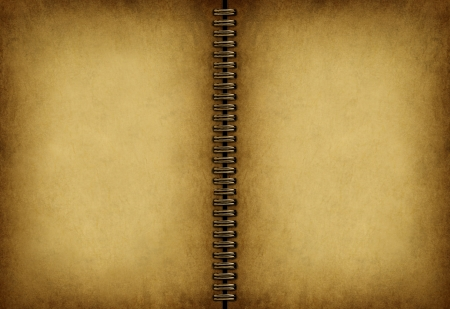 Blank old note book with an antique weathered grunge parchment texture as an empty beige vintage pad with a metal coil in the middle  Stock Photo - 14345346