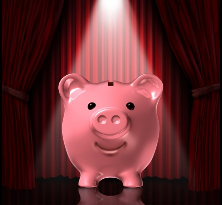 frugality: Focus on savings with a piggy bank in the spot light with elegant rich red velvet curtains as a background as a symbol of financial success and the importance of saving your money  Stock Photo