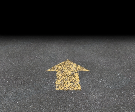Direction Arrow on an asphalt street with an old fading yellow painted road symbol pointing into the black blank distant perspective as a concept of aspirations and financial success vision of strategy and goals  photo