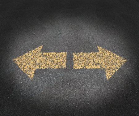 Strategy and decisions concept with a textured asphalt road and two old painted yellow arrows pointing in opposite directions as a business symbol of confusion and uncertainty in the future path ahead