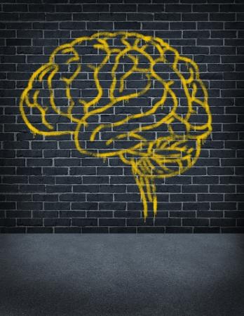 Criminele geest met een gespoten graffiti schilderij van een menselijk brein op een openlucht oud straat bakstenen muur als gezondheidszorg en juridische symbool van crimineel gedrag en problemen in sociaal gedrag