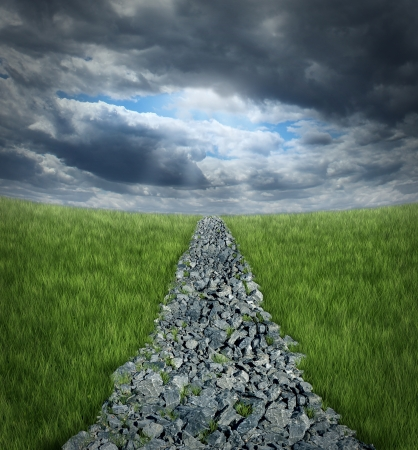 adversity: Conquering adversity and overcoming business challenges ahaead with a bumpy highway path made of rough rocks leading into a perspective horizon with storm clouds and a glimmer of sun shinning through the dark sky