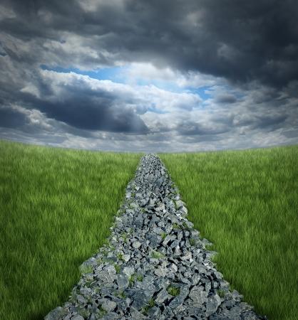 Conquering tegenspoed en het overwinnen van uitdagingen ahaead met een hobbelige weg pad gemaakt van ruwe rotsen leidt naar een perspectief horizon met storm wolken en een glimp van zon shinning door de donkere hemel Stockfoto