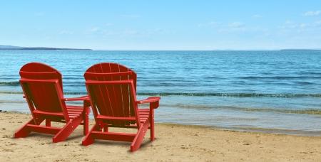 strandstoel: Pensioen Ambities en financiële planning symbool met twee lege blauwe Adirondack stoelen zitten op een tropisch zandstrand met uitzicht op de oceaan als een business concept van de toekomstige succesvolle beleggingsstrategie Stockfoto
