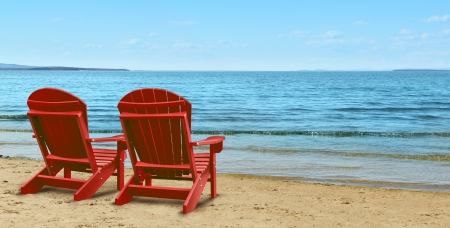 Retirement Aspirations and financial planning symbol with two empty blue adirondack chairs sitting on a tropical sandy beach with ocean view as a business concept of future successful investment strategy  photo