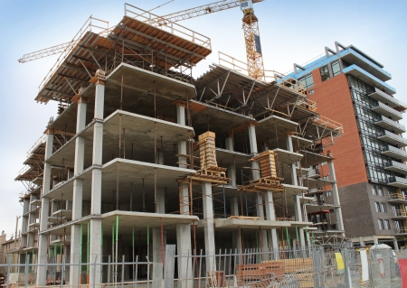 High rise contruction site with a concrete structure in the process of being built as a commercial real estate structure and a business symbol of economic and financial growth and healthy economy  Stock Photo - 15501008