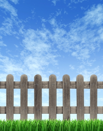 Picket wood fence on a blue sky with green grass in the foreground with weathered old grunge texture as a residential design element  photo
