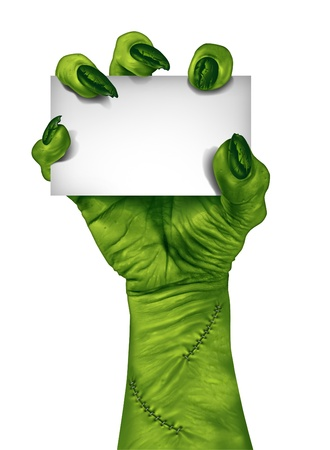Zombie hand holding a blank sign card as a creepy halloween or scary symbol with textured green skin wrinkled monster fingers and stitches isolated on a white background   photo