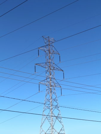 Electricity pylon and high tension metal structure transporting hydro power  through insulated cables and wires as part of the traditional energy grid with electric lines criss cossing forming a pattern against a blue sky Stock Photo - 15739396