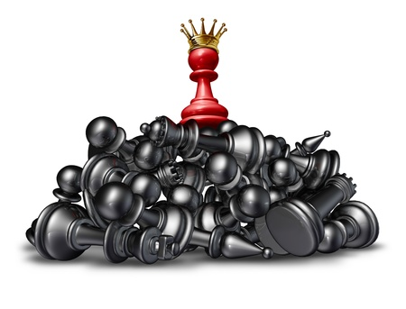 The winner and the victor success concept with a red chess pawn wearing a gold crown on top of a mountain of defeated competitors that are lying down against a white background  photo