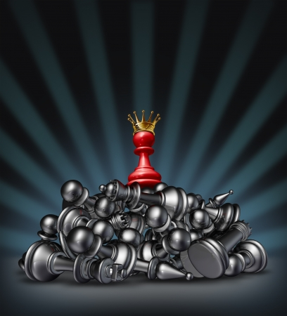 Victory and the winner as a success concept with a red chess pawn wearing a gold crown on top of a mountain of defeated competitors that are lying down against a black background with a star burst light  photo