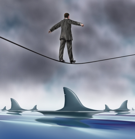 overcome: Courage and risk business concept with a business man in a grey suit walking on a tightrope with dangerouse sharks circling underneath as a risk and symbol of determination and strength  Stock Photo