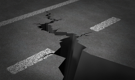 earthquake: Failed strategy and journey problems with an asphalt highway with painted lines and broken by a huge crack splitting the road into two parts as business or life concept of road blocks and challenging obstacles to a planned path  Stock Photo