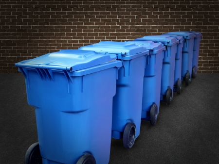consummation: Recycle bins in a group made of commercial size blue plastic containers in a city street back alley against a brick wall as a conservation and recycling symbol of business environmental responsability