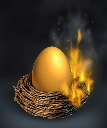 overspending: Savings crisis with a burning golden nest egg going up in flames as a financial concept of money despair and challenges managing debt problems due to economic downturn or overspending and going over budget  Stock Photo