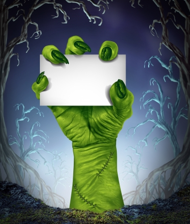 creepy monster: Zombie rising hand holding a blank sign card as a spooky halloween or scary symbol with textured green skin and monster fingers with stitches in a foggy night time tree forest background as a cemetary like creepy place  Stock Photo