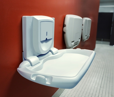 diaper changing table: Urban parenting with a public diaper changing table mounted on a wall