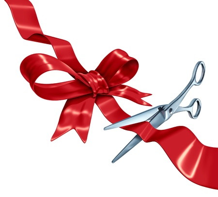 scissors cutting paper: Bow and ribbon cutting with a red silk gift wrapping decoration with scissors opening the present packaging as a holiday symbol for Christmas a birthday or valentine