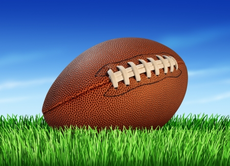 Football ball on a grass field and a blue sky as a professional or college game sport for traditional American and Canadian play