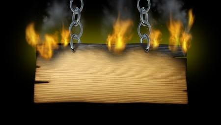 advertise: Burning wooden sign with fire flames and smoke on an old wood plank with metal chains holding the signage as a western or rustic hot message advertisement on a black background  Stock Photo