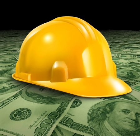 Construction business with a yellow hardhat helmet on a floor of money and currency representing the economic condition of commercial and residential building activity and investment  Zdjęcie Seryjne