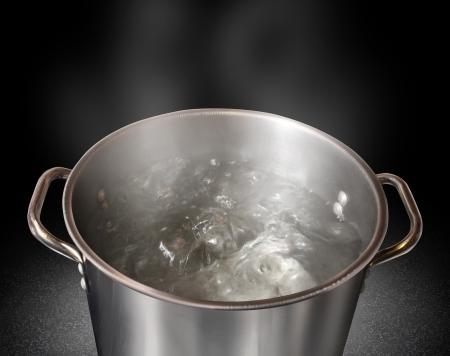 water contamination: Hervir el agua en una olla de cocina como s�mbolo de cocinar o preparar alimentos y la esterilizaci�n del agua del grifo contaminada por l�quido sano potable sobre un fondo negro Foto de archivo