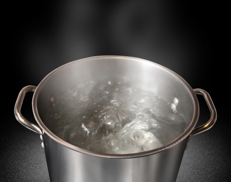 Boiling water in a kitchen pot as a symbol of cooking or food preparation and sterilization of contaminated tap water for healthy pure drinking liquid on a black background