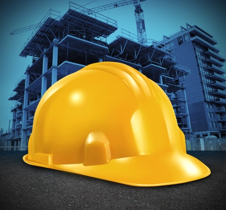 commercial activity: Construction industry and commercial real estate business investment with a yellow builder hard hat and a high rise structure being built as a symbol of economic and financial growth and healthy economy  Stock Photo