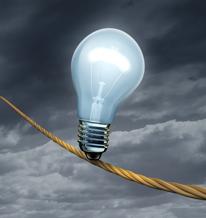 heavy risk: an illuminated light bulb on a high dangerous risky tightrope on a storm sky