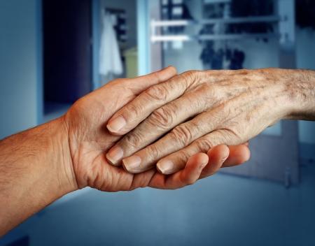 сообщество: Престарелыми и старших медицинских услуг с руки молодого человека и помогать проведения старые и старения отставной пациент нуждается в домашнем медицинской помощью из-за старения и потери памяти в больнице фоне Фото со стока