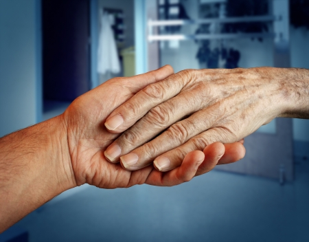 Elderly care and senior health services with the hand of a young person holding and helping an old and aging retired patient needing in home medical help due to aging and memory loss in a hospital background