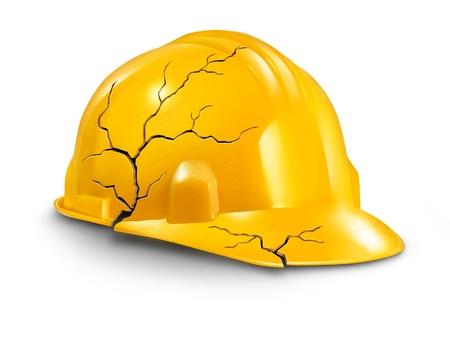 accidente laboral: Accidente de trabajo y riesgos para la salud en el trabajo como un casco roto agrietado casco amarillo como s�mbolo de las demandas por lesiones de trabajo y el seguro de da�os f�sicos y dolor al trabajador Foto de archivo