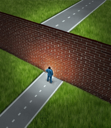 road block: Business challenge and financial obstacles concept with a businessman standing in front of a large brick wall that has blocked his path and obstructed a journey to success Stock Photo