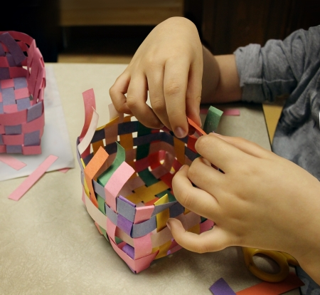 crafting: Artes y oficios con las manos de un ni�o que hacen a mano una cesta hecha de cartulina como s�mbolo de la educaci�n art�stica en las escuelas u otras actividades creativas para ni�os Foto de archivo