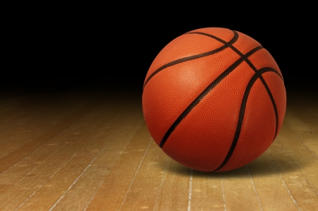 college basketball: Basketball on a hardwood court floor as a sports and fitness symbol of a team leisure activity playing with a leather ball dribbling and passing in competition tournaments
