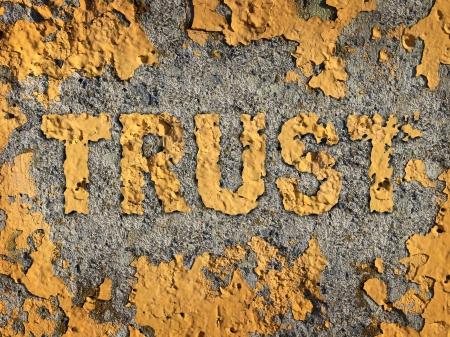 desconfianza: La pérdida de confianza y el deterioro de la integridad como un concepto de negocio representado por edad fading pintura amarilla agrietada en una pared de cemento áspero que muestra la metáfora de negocios de la moral perdida y banco financiera ilegal y las poblaciones de las transacciones