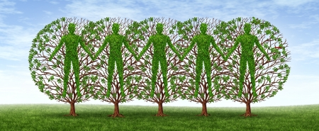 Community and friendship concept with a group of trees in the shape of people holding hands together in harmony as a growing partnership in a strong cooperation on a blue sky