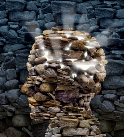dementia: Power of thinking and free your mind as a business or health care concept with a group of rocks in the shape of a human head glowing with a bright inner light as a symbol of freedom and intelligence