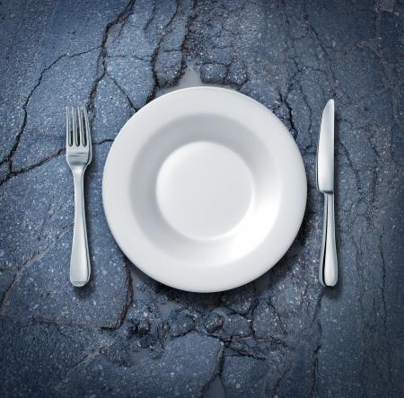 プレート: 通りの食糧および供給、貧乏人がホームレスされ、古い汚れた街アスファルトにナイフとフォークを空の白い板で空腹の不健康な食べるか、または都市の料理のコンセプトとして