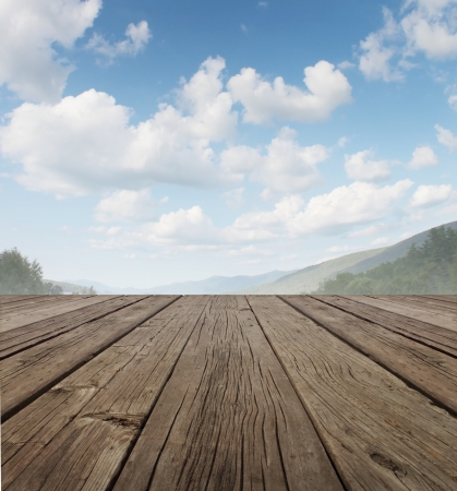Wood deck as a tranquil old rustic country patio floor in perspective with a summer sky on a beautiful mountain range with forest trees as a symbol of travel and backyard living