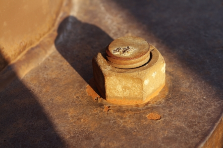 Dying industry and old industries as a business concept with an antique industrial rusted nut and bolt with the sun lighting setting on a market segment that is losing profitability and the needs modernisation  photo