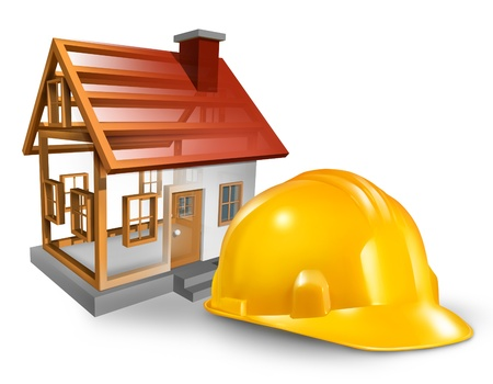 House construction and home builder concept with a yellow worker hardhat and a residential structure being built on a white background