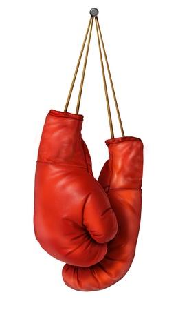 Bokshandschoenen opknoping op een afgelegen witte achtergrond met veters genageld aan een muur als een bedrijf of sport concept van een persoon die met pensioen geeft de strijd of bereidt zich voor op de concurrentie Stockfoto