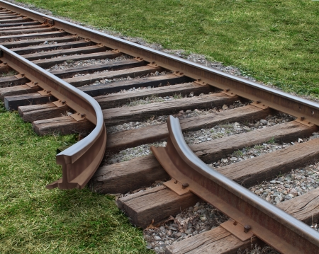 off track: Strategy obstruction challenges with a train track that is broken as a business concept of a road block and finding solutions to obstacles that are dangerous and challenging as  journey on a strategic goal  Stock Photo