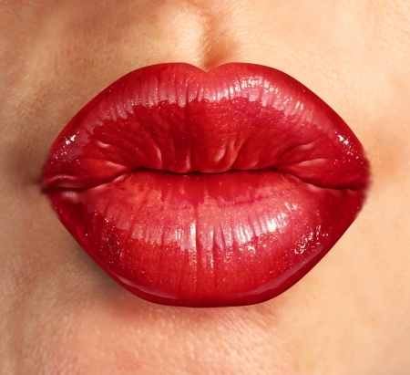 Human kiss lips with glamorous glossy red lipstick on the face of an attractive beautiful woman as a beauty and health concept pertaining to cosmetics and female business fashion